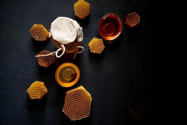 항아리와 벌집에 꿀입니다. 검은 나무 배경에. 텍스트를 위한 여유 공간입니다. 평면도.