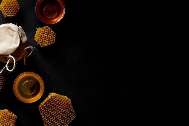 Мед в банке и сотах. на черном деревянном фоне. свободное место для текста. вид сверху.
