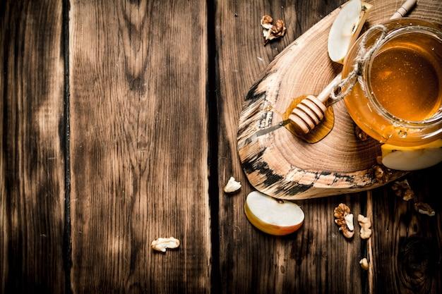 ナッツとリンゴのスライスが入った瓶の中の蜂蜜。木製の背景に。