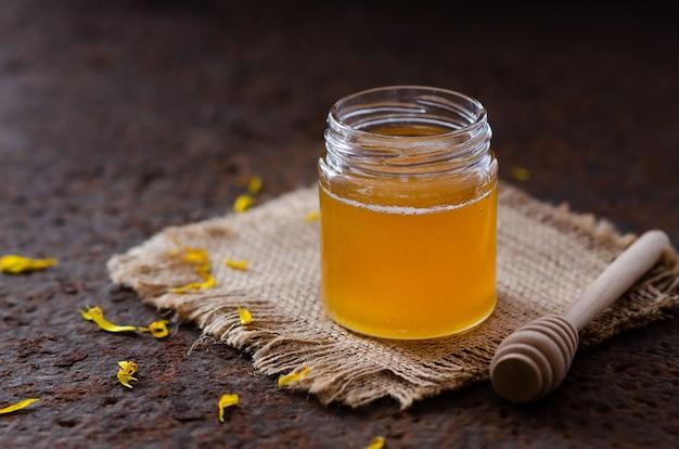 黄色いデイジーの花びらとハニーディッパーが入った瓶の中の蜂蜜