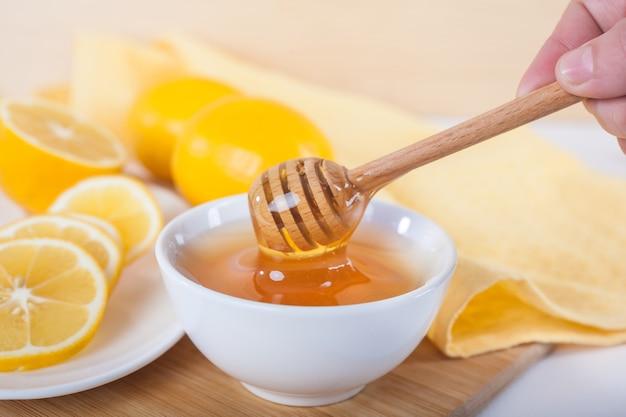 木製のキッチンボードに蜂蜜ディッパーとレモンと白いセラミックボウルの蜂蜜。