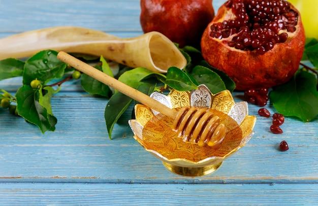Мед в миске с палочкой и гранатами