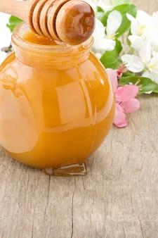 ガラスの瓶に蜂蜜と花の花に固執する