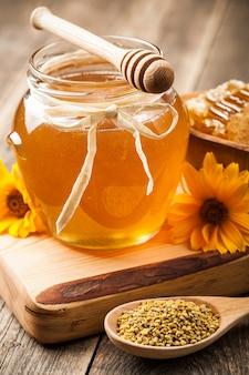 木製のテーブルの上のガラス瓶の蜂蜜