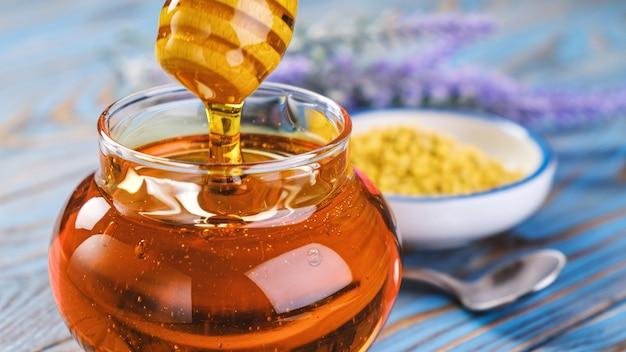 벌집과 프로 폴리스, 액체 설탕 시럽, 꽃 꿀 나무 배경 위에 꿀 국자와 유리 항아리에 꿀