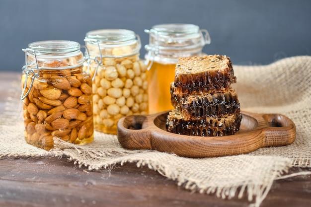 Мед в сотах на деревянной тарелке. баночки с медом, миндалем и фундуком