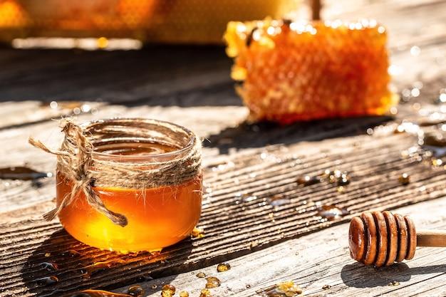 Мед в банке с ковшом для меда, соты с полными ячейками меда на старинном деревянном фоне