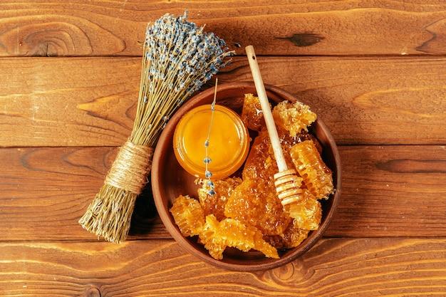 ヴィンテージ木製の背景にハニーディッパーと瓶の蜂蜜