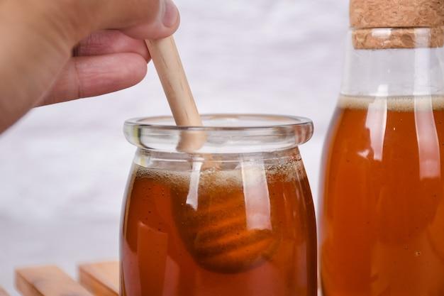 あなたのテキストのための白い背景の上のハニーディッパーと瓶の中の蜂蜜
