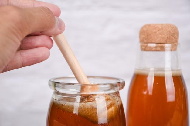 白い背景の上のハニーディッパーと瓶の中の蜂蜜コピースペース