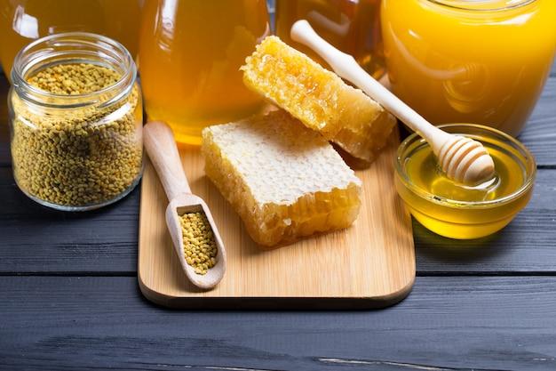 Мед в банке с ковшом для меда на деревянных фоне