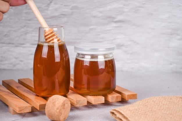 テーブルの上の木製のハニーディッパーと瓶の中の蜂蜜コピースペース