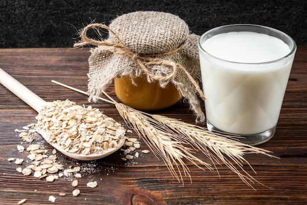 Банка меда и стакан молока на темном деревянном столе.