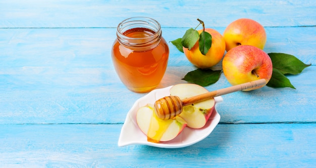 Honey jar and apple slices with honey on blue wooden background