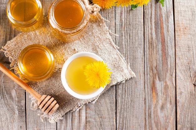 蜂蜜の瓶、木製のテーブルの上のタンポポの花