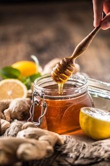 나무 테이블에 꿀 항아리 디퍼 생강 레몬과 민트 허브.