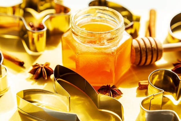 Honey jar, honey dipper and cookie cutters on yellow background. preparing to bake cookies. bright sunshine