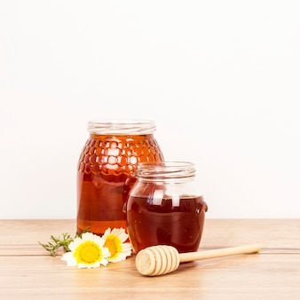 Honey jar and honey dipper with white flower over wooden surface