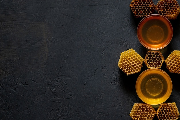 Honey in a jar and a honeycomb. on a black wooden background. free space for text. top view.