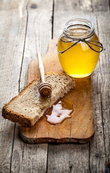 Honey in a jar, slice of bread, wheat and milk on an old vintage planked wood table from above. rural or rustic style breakfast concept.