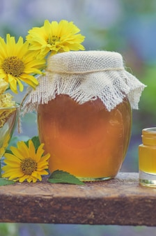 Honey in jar with honey dipper on rustic wooden table. sweet honey in the comb. healthy food concept. honey products by organic ingredients.