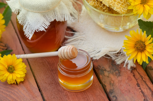 Honey in jar with honey dipper on rustic wooden table