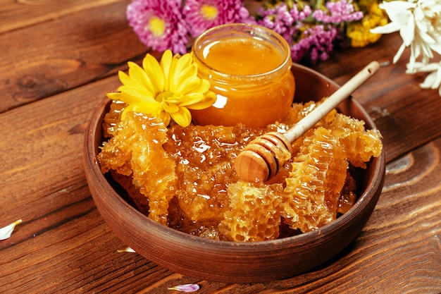 Honey in jar with honey dipper on vintage wood