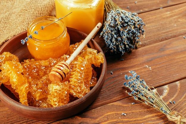 Honey in jar with honey dipper on vintage wooden