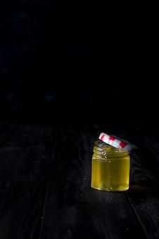 Honey jar with a wooden stick drains honey on an dark background