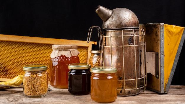 Vasetti di miele con fumatore di api e favo