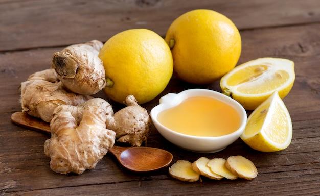 Мед, лимон и имбирь на деревянном столе крупным планом