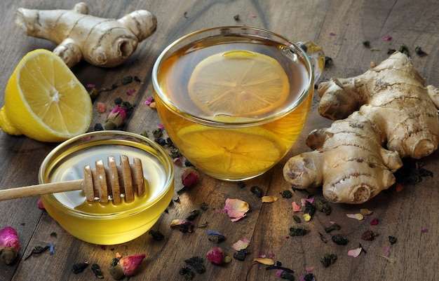 蜂蜜、レモン、生姜、木製のテーブルにレモンとお茶のカップ。伝統的な風邪薬