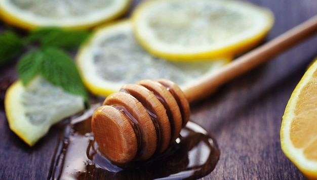 Honey and lemon. honey stick and slices of sliced lemon on wooden table. tea in a cup and sweet lime honey in a jar.