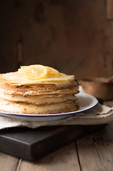 Honey or maple syrup pouring over crepes. closeup view of stack of thin pancakes, blini