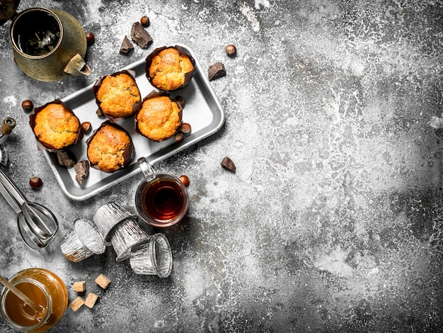 Honey muffins with fragrant tea on rustic table.