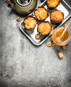 Honey muffins with a teapot on rustic table.