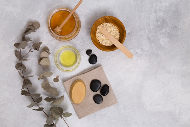 Honey; oats; oil; soap and la stone on napkin with dried eucalyptus populus leaves on concrete backdrop