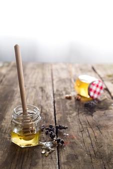 Мед органический в банке с деревянной палочкой на старом деревянном фоне