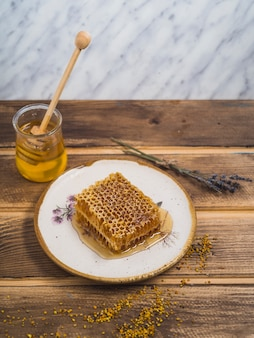 Honey piece on wooden white plate with lavender and bee pollens on wooden table