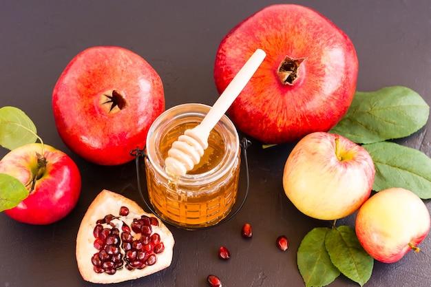 Мед, гранат и яблоки на черном столе. еврейский праздник рош ха-шана фон.