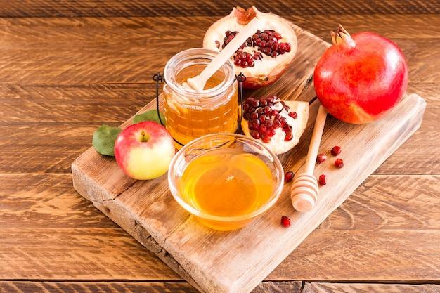 Мед, гранат и яблоки на деревянном столе. еврейский праздник рош ха-шана фон.