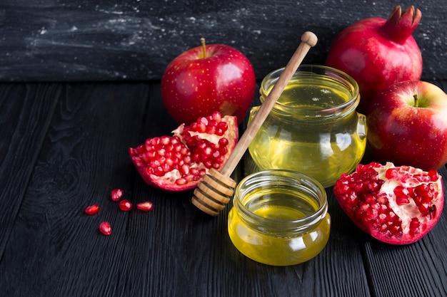 Мед, гранат и красные яблоки на черном фоне