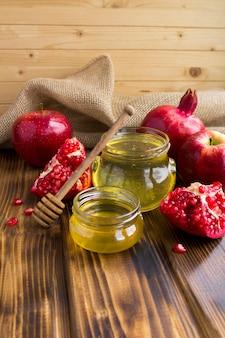 Мед, гранат и красные яблоки на деревянном деревенском фоне