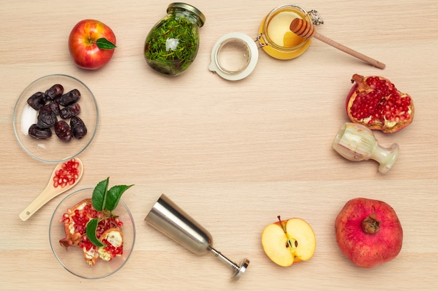 Honey, pomegranate, apple and dates on wooden board