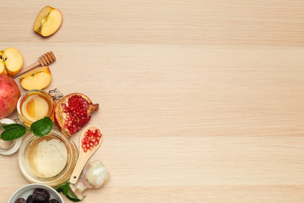 Honey, pomegranate, apple and dates on wooden board.