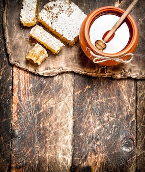 Горшок меда и соты деревянной ложкой. на деревянном фоне.