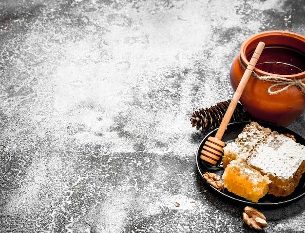 Горшок меда и соты с грецкими орехами. на деревенском фоне.