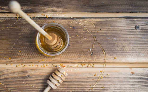 Honey pot and bee pollens on wooden table