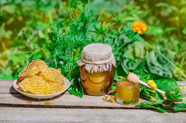 Honey pot, dipper, jar of fresh honey,  honeycomb on a wooden table outdoors
