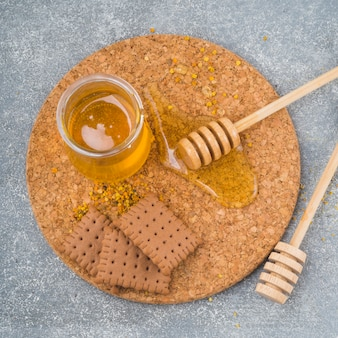 Honey pot; wooden dipper; biscuits and bee pollen on cork coaster